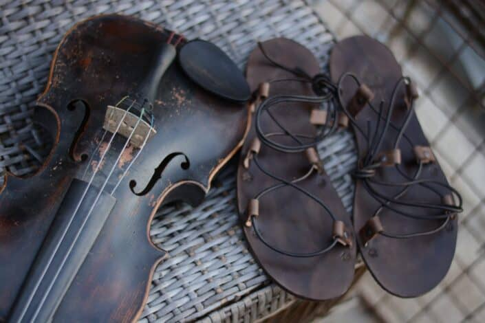 pair of rustic sandals beside a violin