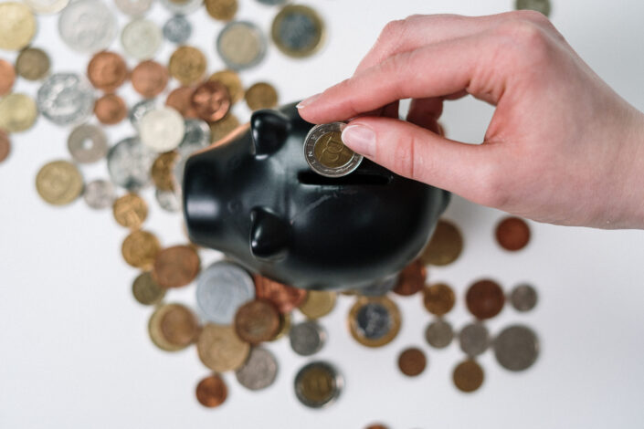 A piggy bank being inserted with some coins.