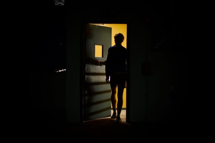 A silhouette of a man opening the door.