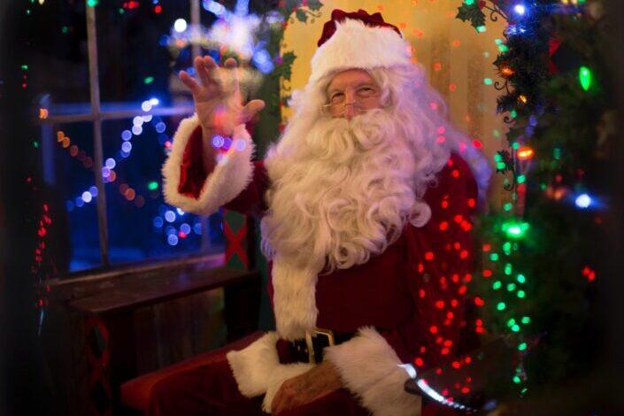 Man in a Santa costume waving.