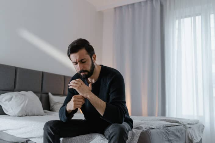 miserable looking man sitting on his bed
