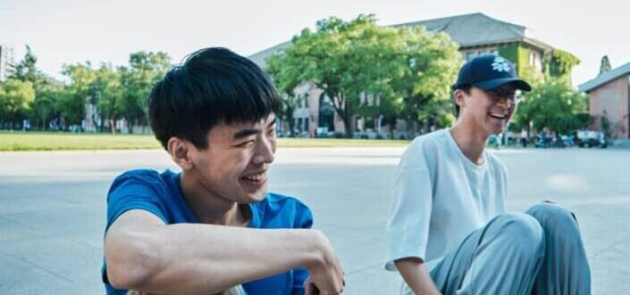 Two guys sitting along the highway, laughing